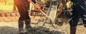 Worker poring cement at construction site